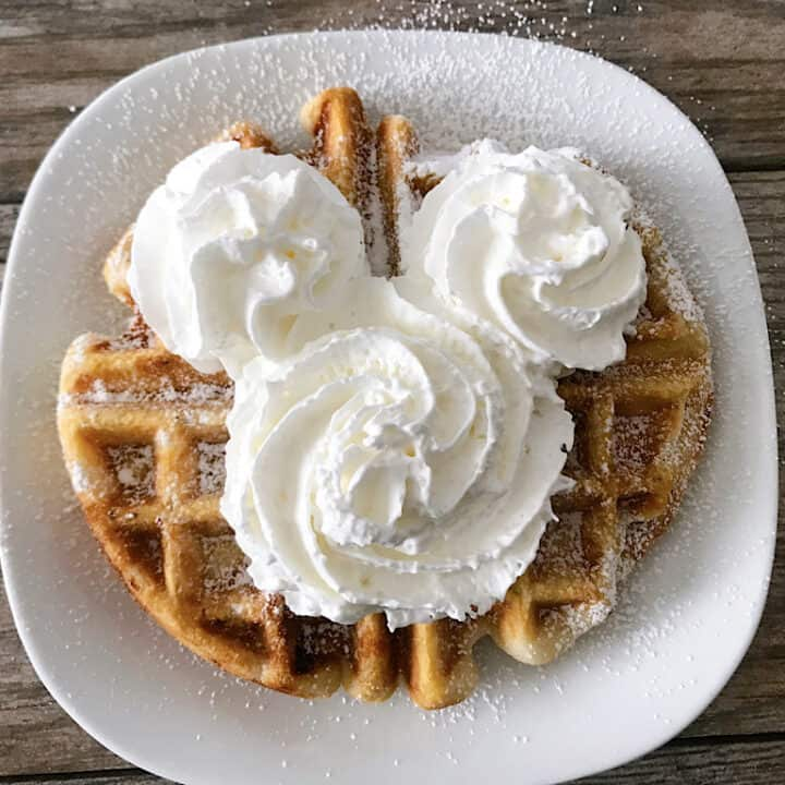 A funnel cake waffle with Mickey Mouse-shaped whipped cream