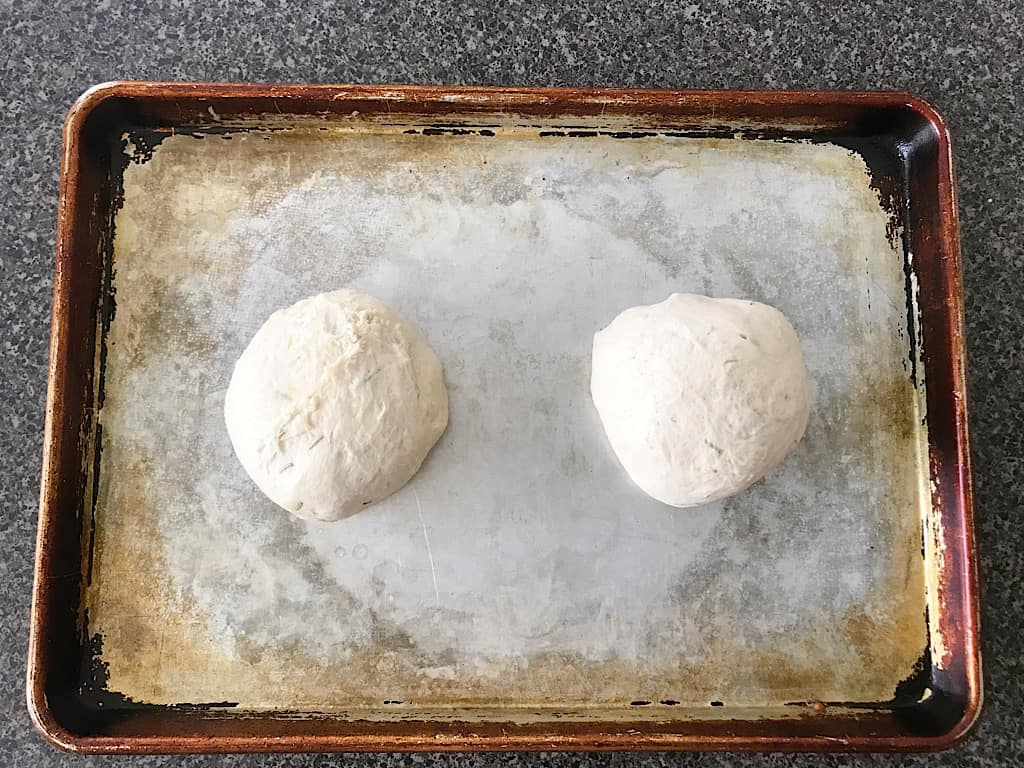 Punch down the dough and divide it in half. Shape the dough into two oval/square loaves and place them on a greased baking sheet.