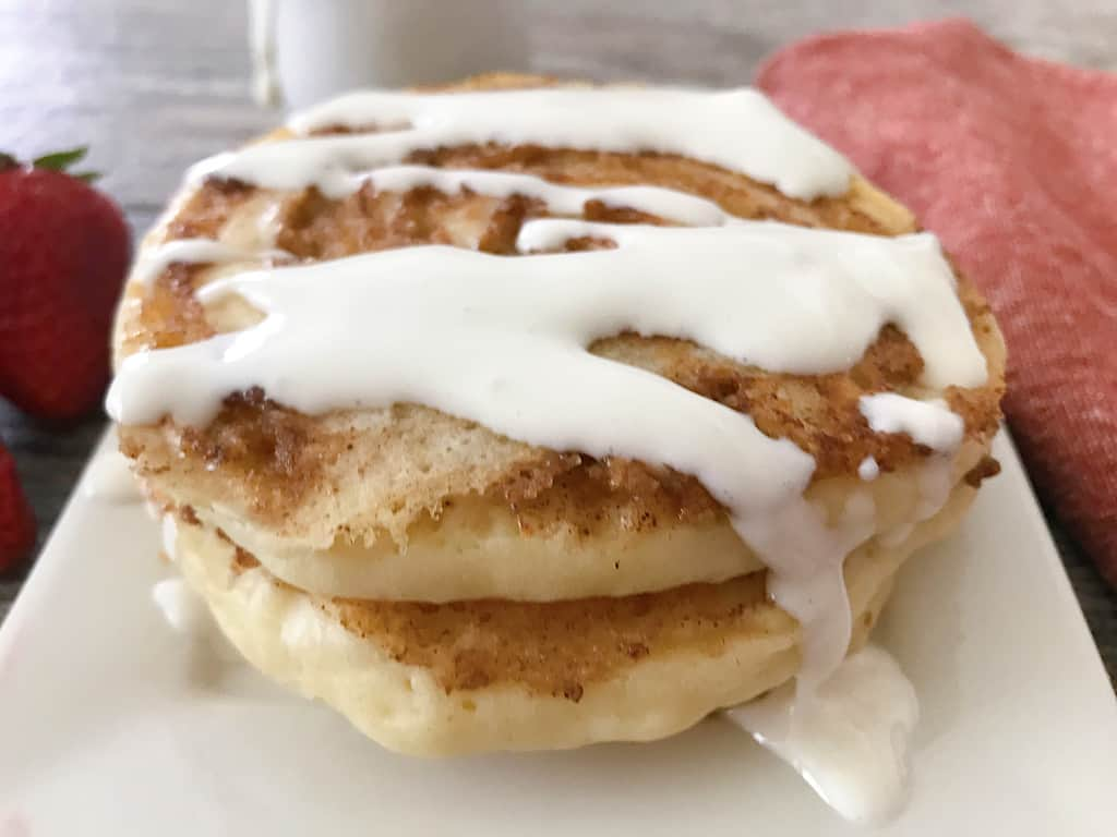 Cinnamon roll pancakes drizzled with cream cheese icing