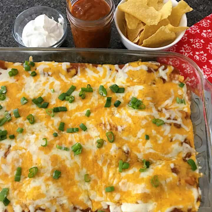 A pan of cheese enchiladas, a bowl of tortilla chips and sour cream