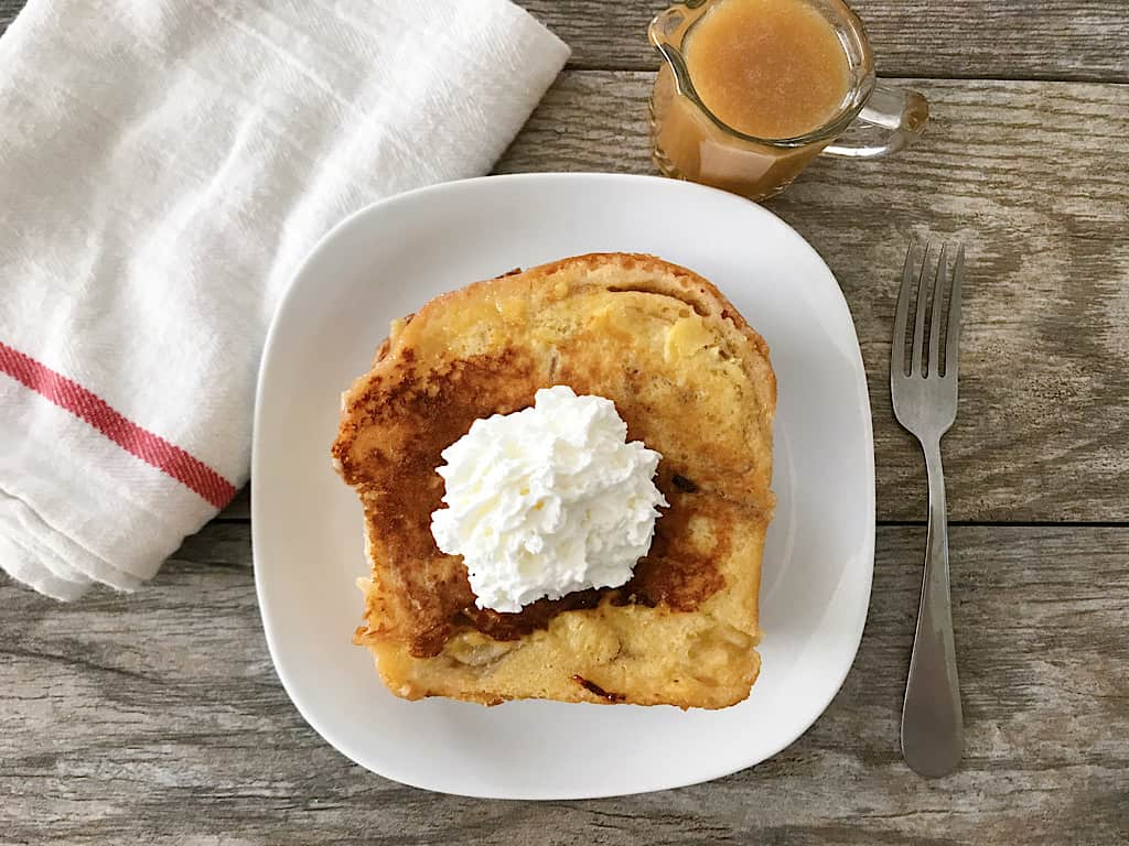 Chunky Cinnamon French Toast with whipped cream and a cup of caramel syrup