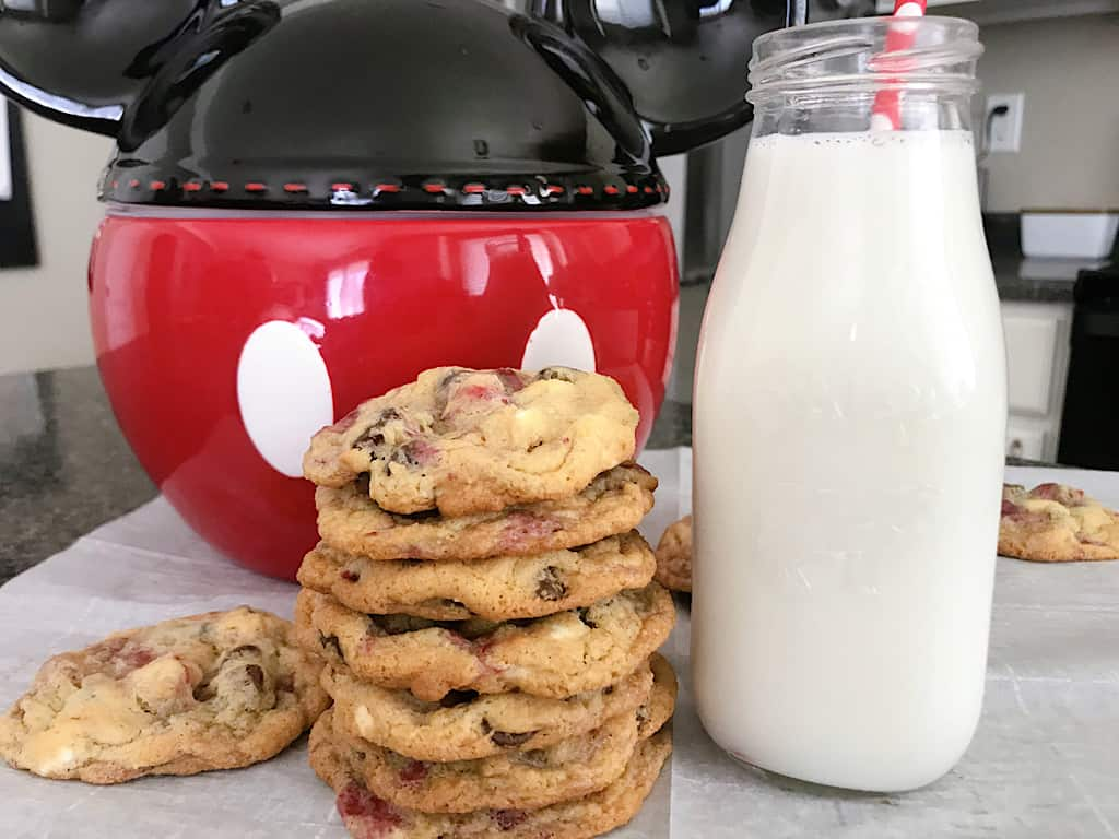 Disneyland Raspberry White Chip Cookies with a glass of milk and a Mickey Mouse Cookie Jar