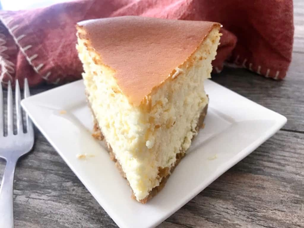 A slice o New York Cheesecake on a white plate.