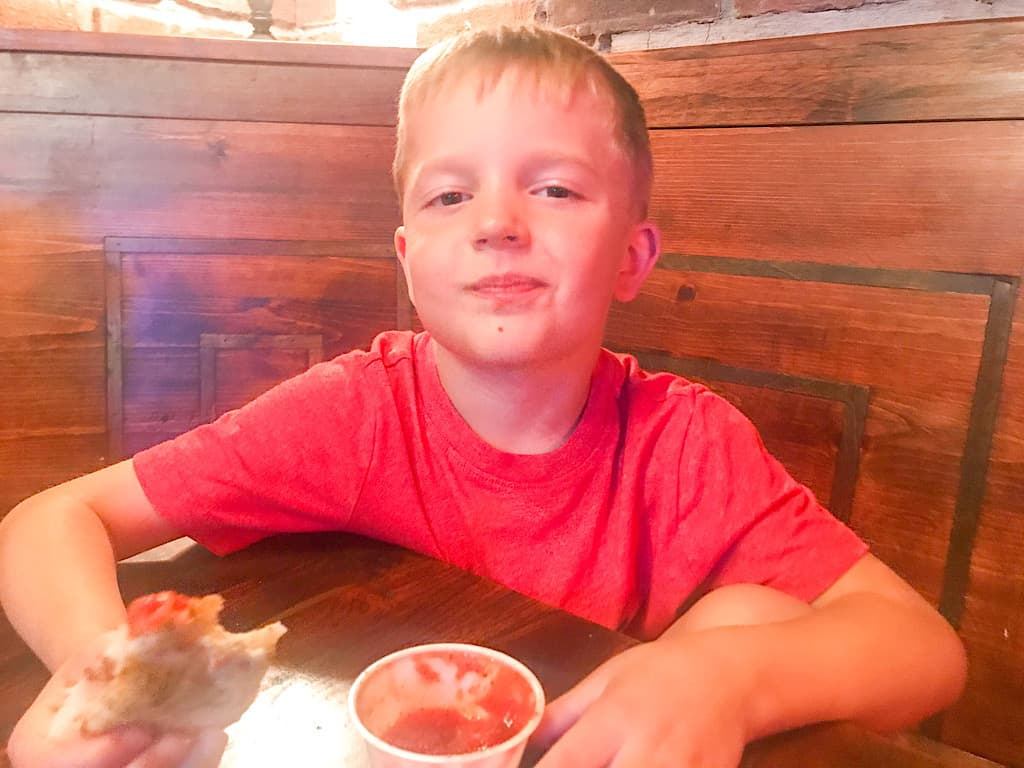 A boy eating pizza at Pinky G's Pizzeria in Jackson Hole, Wyoming