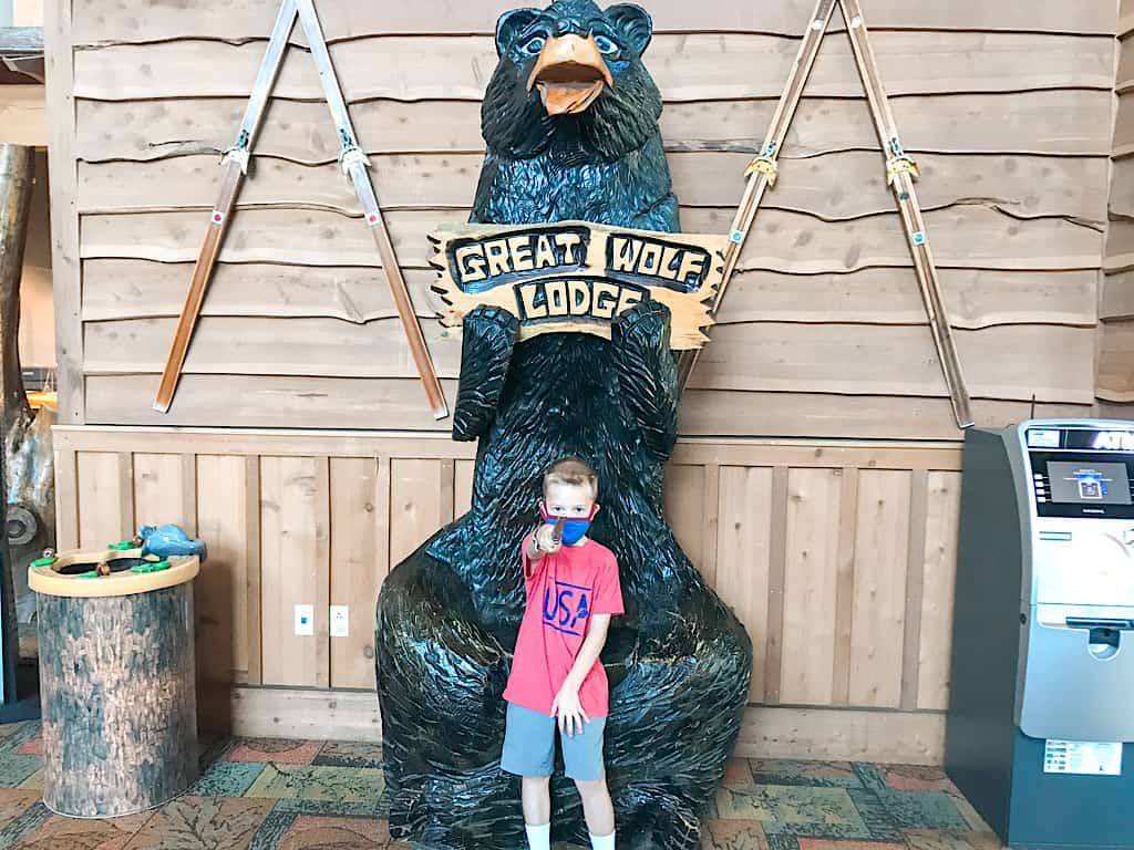 A child in front of a wooden bear with a sign that says Great Wolf Lodge