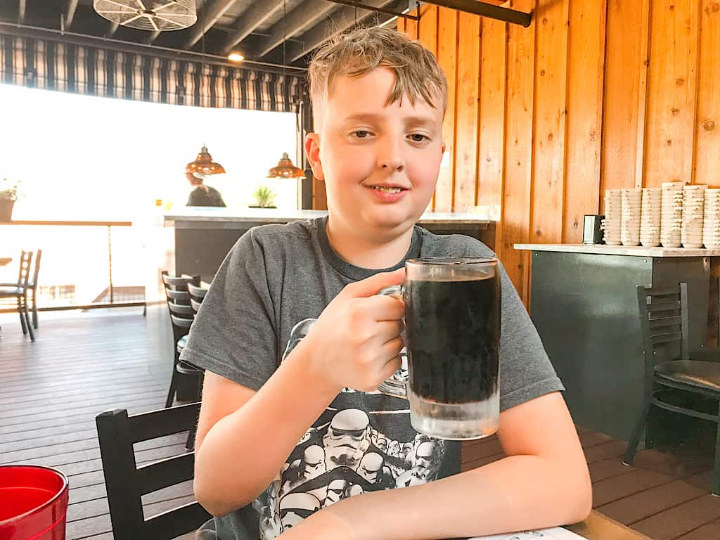 A boy with a mug of root beer at Zax Restaurant in Moab, Utah