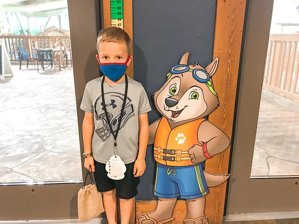 A child next to a cartoon wolf at Great Wolf Lodge water park