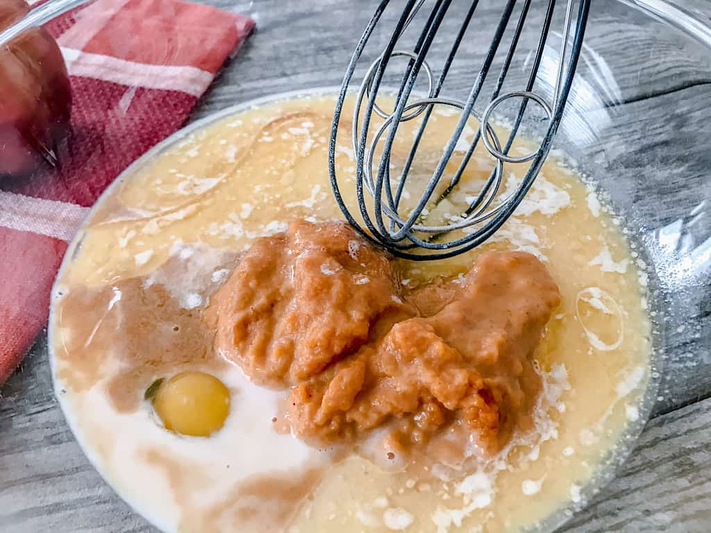 In a separate bowl, whisk together the eggs, brown sugar, pumpkin puree, milk, melted butter, and vanilla extract.