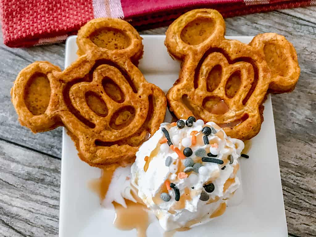 Two Pumpkin spice Mickey waffles with a scoop of ice cream and sprinkles.