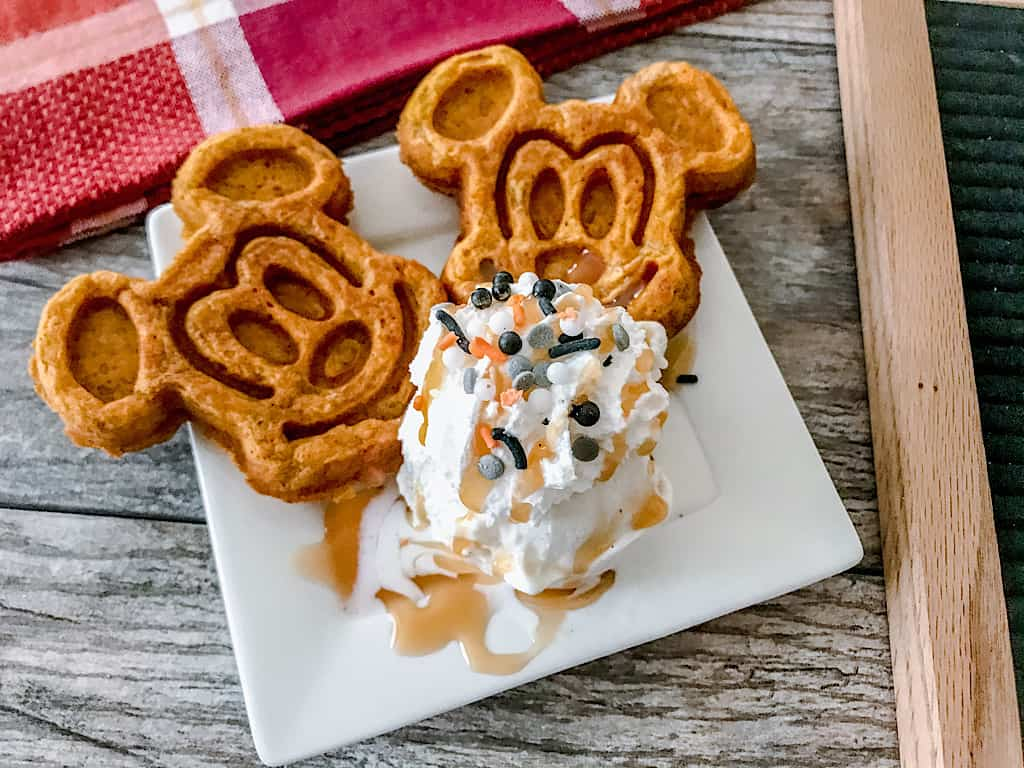 Two pumpkin mickey waffles with ice cream, whipped cream, caramel, and sprinkles.