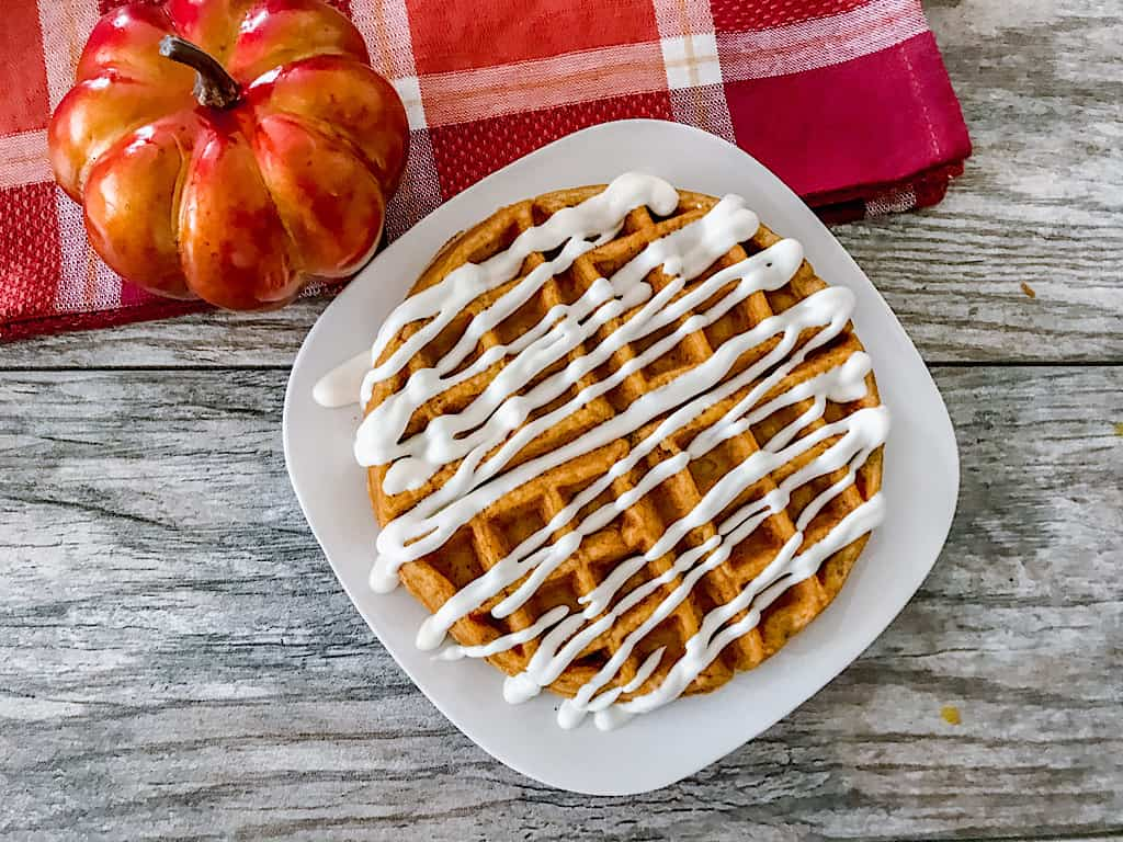 a pumpkin waffle drizzled with cream cheese icing