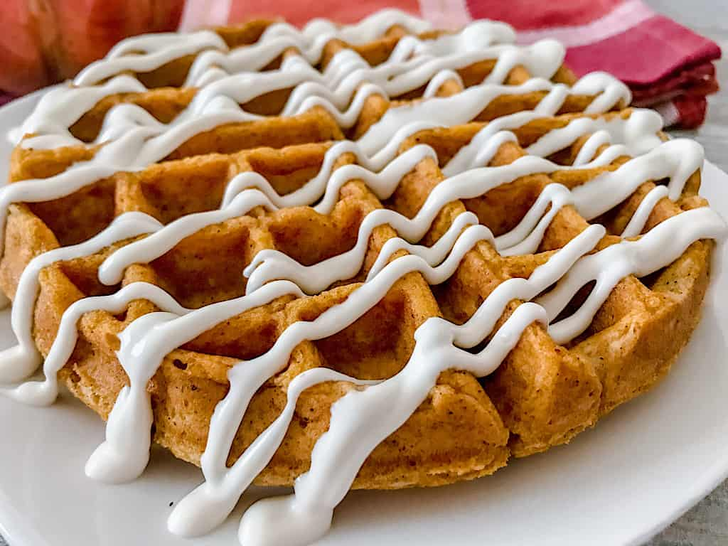 A Pumpkin spice waffle drizzled with cream cheese syrup