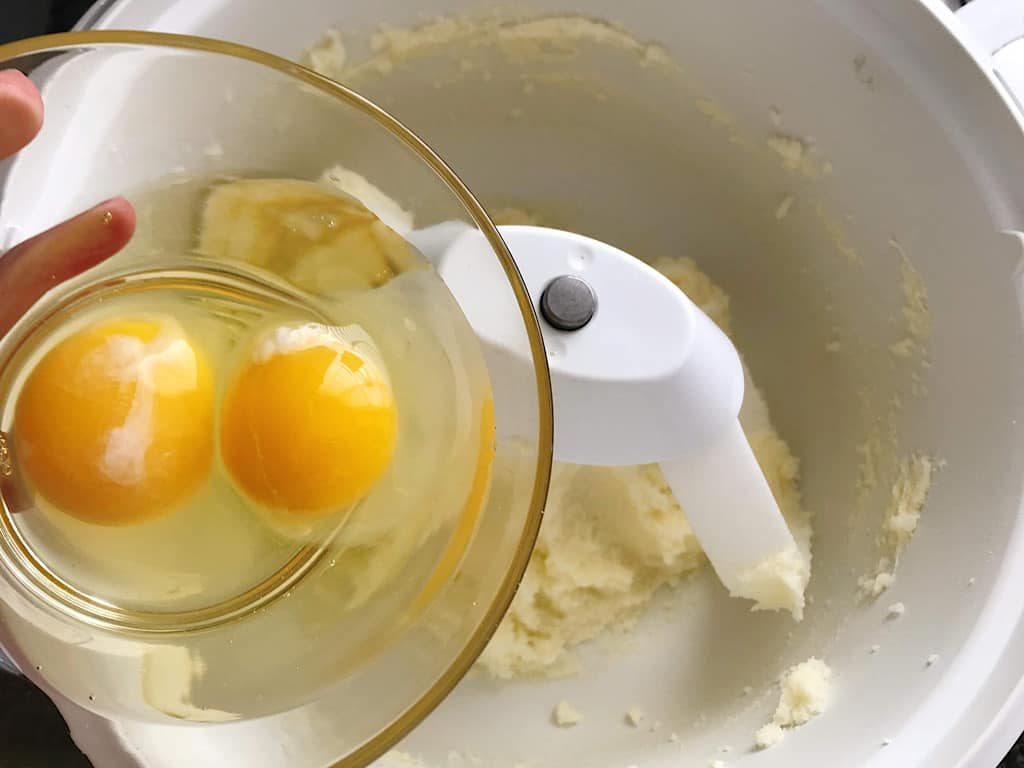 Eggs added to butter and sugar in an electric mixer