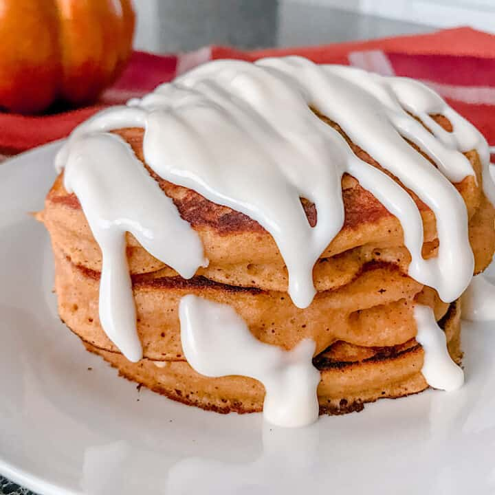 A stack of pumpkin pancakes covered in cream cheese syrup.