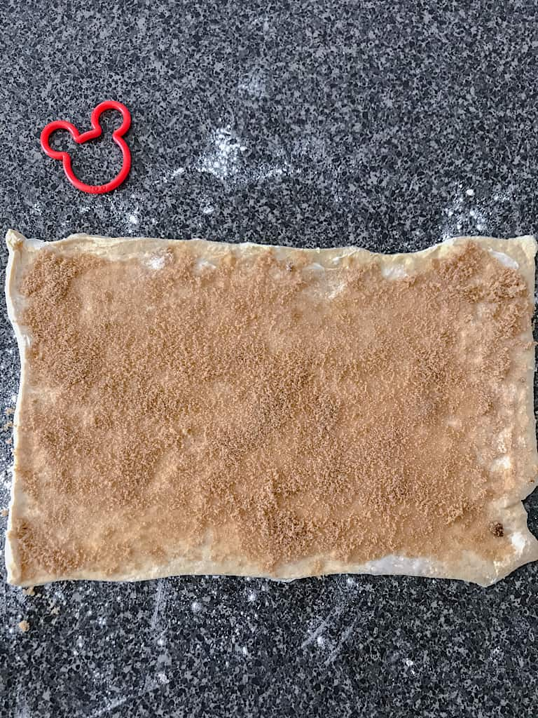 Sprinkle half of the brown sugar over the melted butter on each dough section.