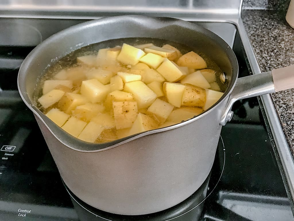 Potatoes boiling in a pan on a stove