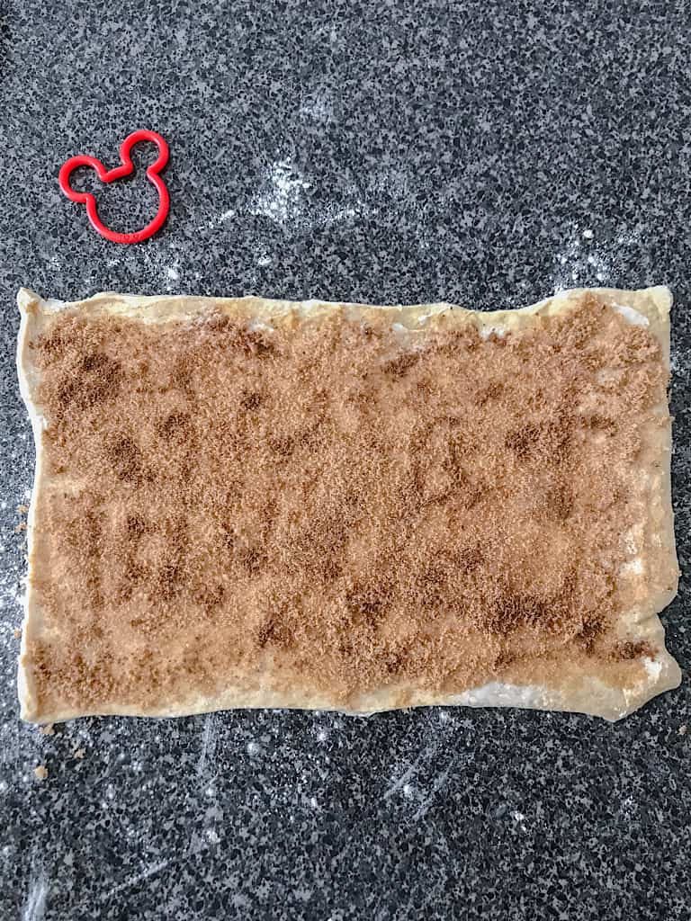Top each of the crescent dough rectangles with 1 teaspoon of cinnamon each.