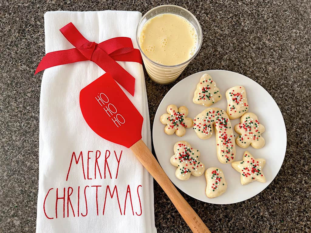 A plate of eggnog sugar cookies with frosting and sprinkles and a towel that says Merry Christmas