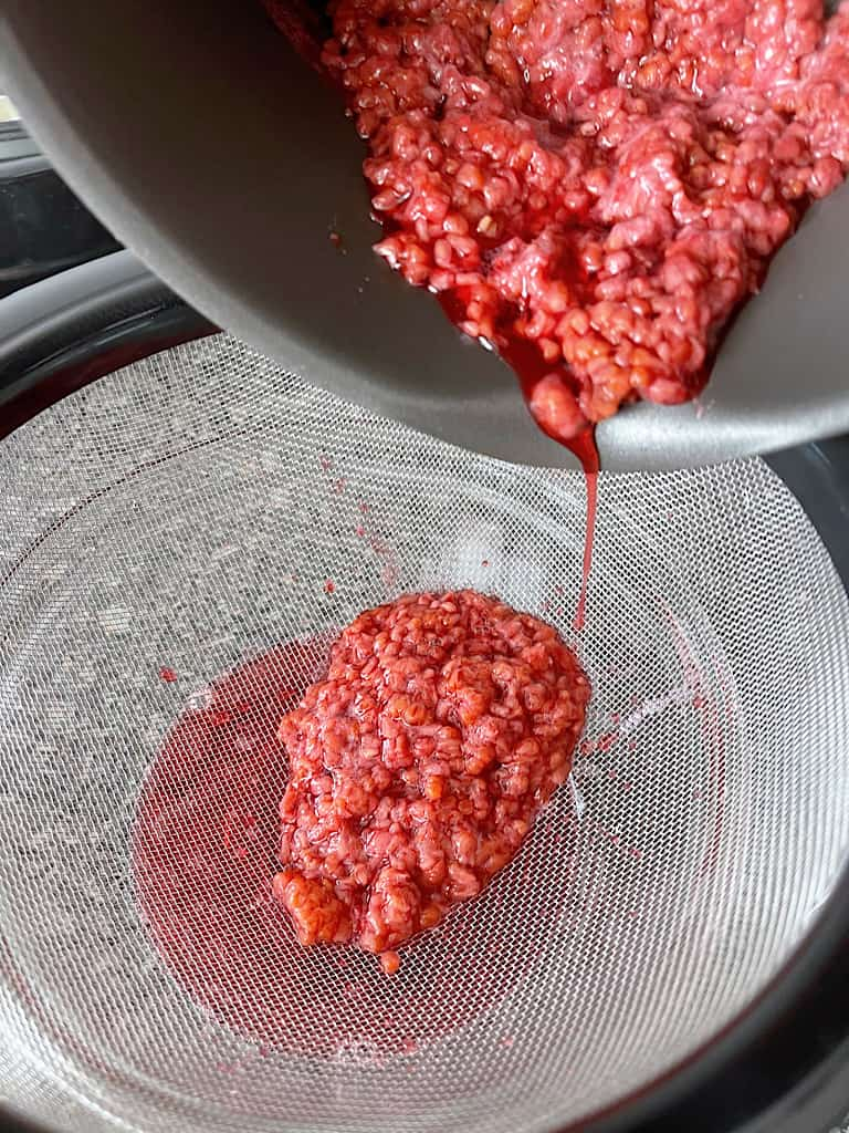Place a mesh strainer over a bowl and pour in the raspberry mixture.