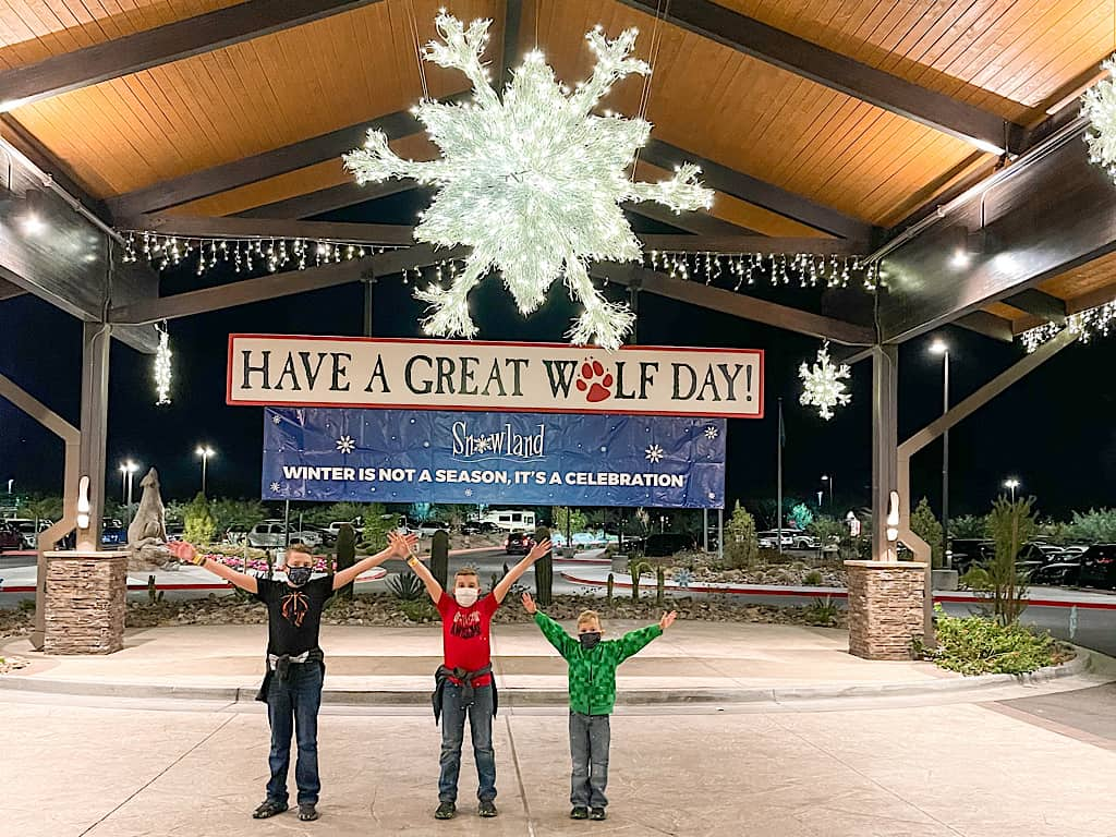 Three kids in face masks at the entrance of Great Wolf Lodge