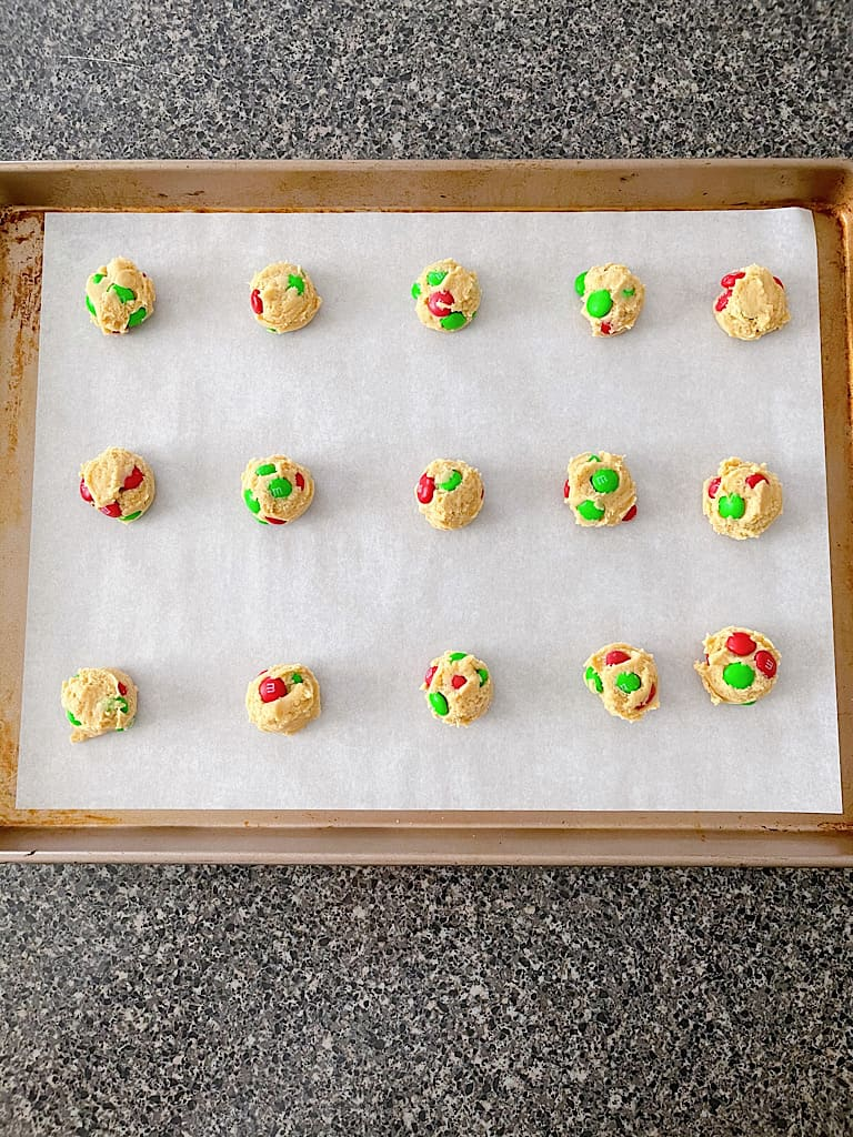After chilling, place the cookie dough balls on a baking sheet lined with parchment paper about two inches apart.