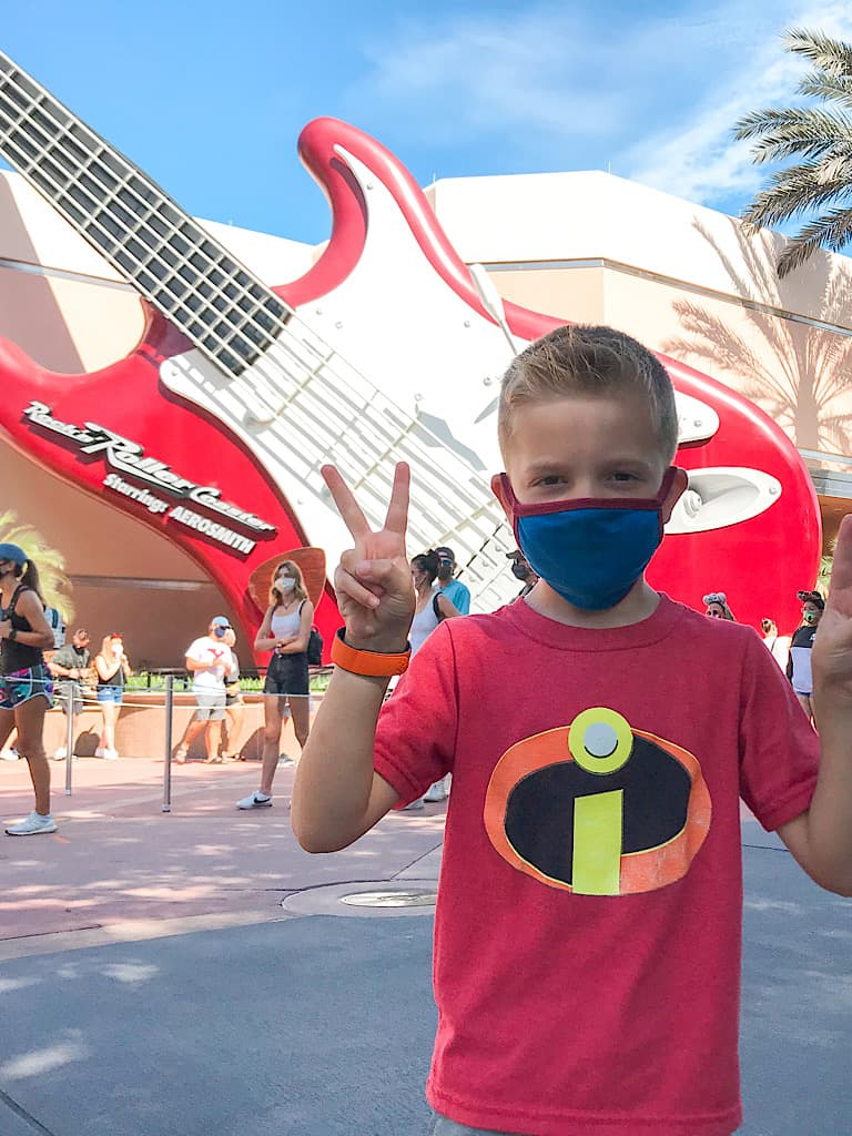 A boy holding up two fingers in front of Rockin' Roller Coaster at Disney's Hollywood Studios