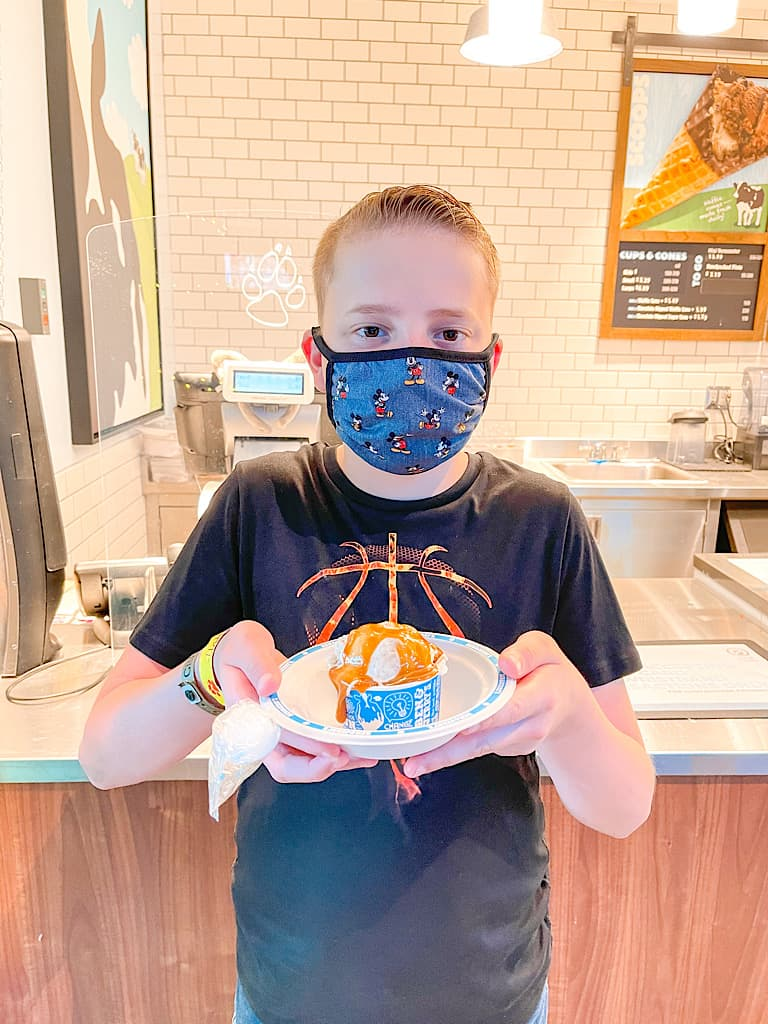 A boy with a mask holding a scoop of ice cream included with a Wolf Pass at Great Wolf Lodge
