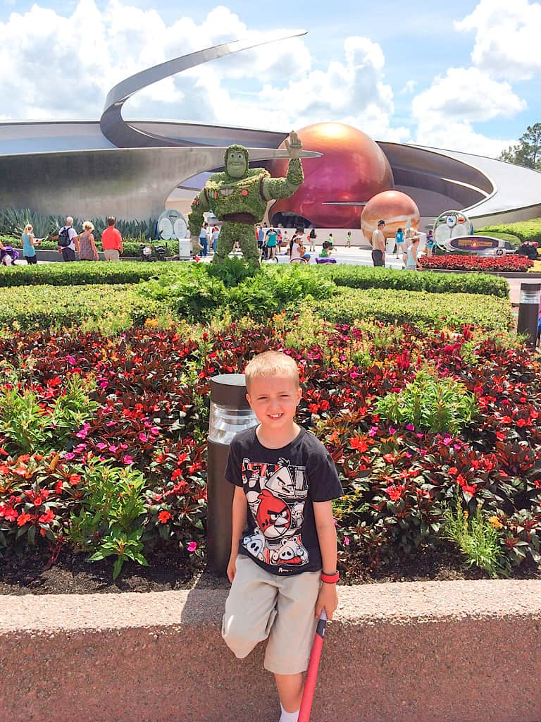 a boy in front of Buzz Lightyear made out of flowers at Epcot International Flower and Garden Festival
