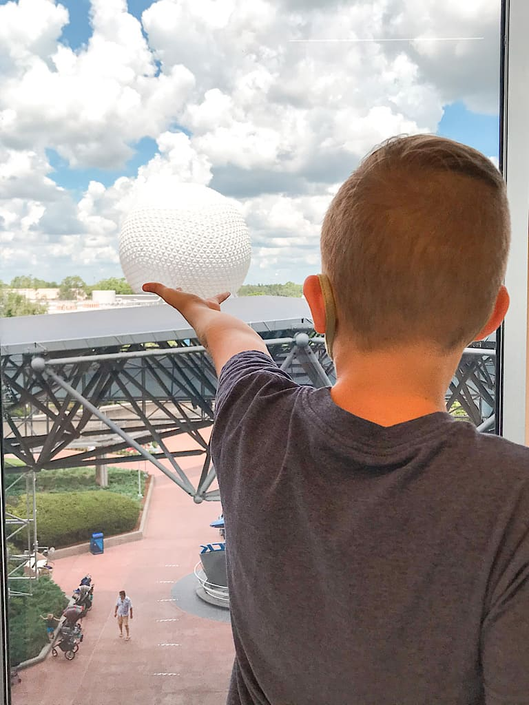 A boy holding out his arm which looks like it is holding up Spaceship Earth at Epcot