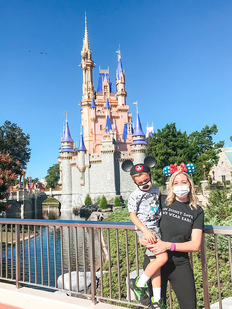 A mom and child in front of Cinderella's Castle