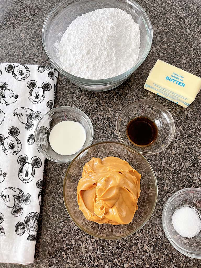 Ingredients for peanut butter frosting including powdered sugar, cream, vanilla, butter, peanut butter, and salt.