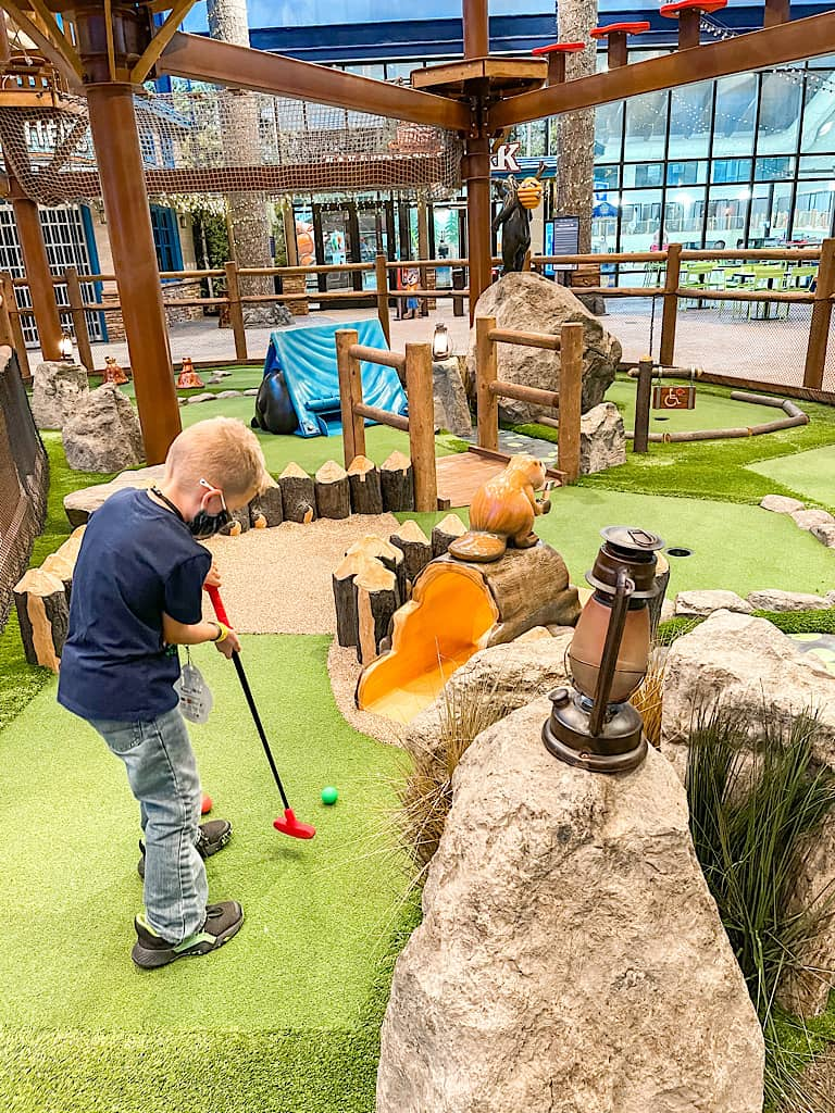 A boy playing mini golf at Great Wolf Lodge