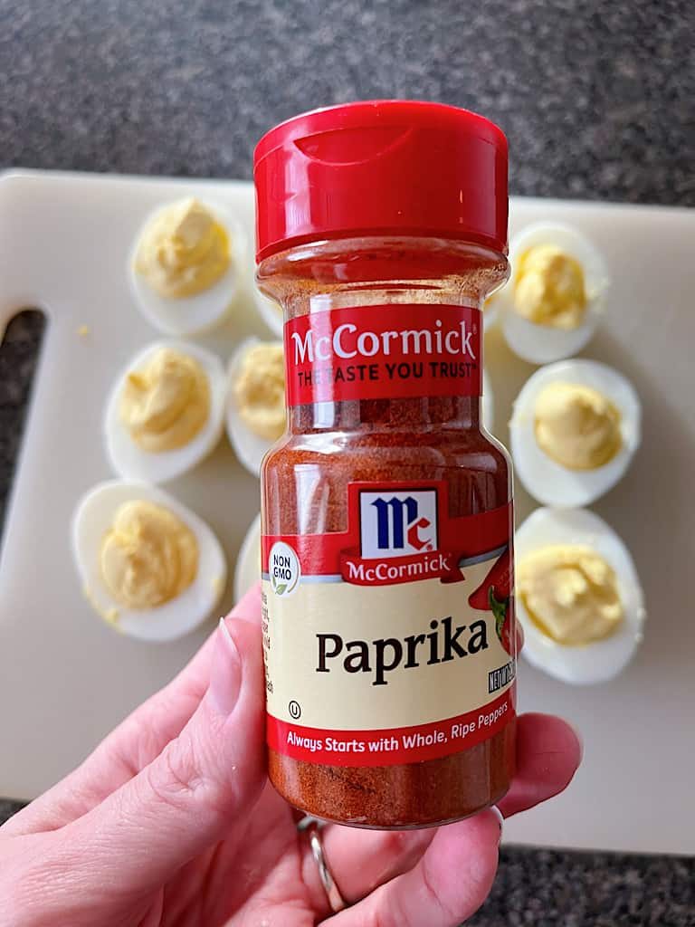 A jar of paprika held over bacon ranch deviled eggs.
