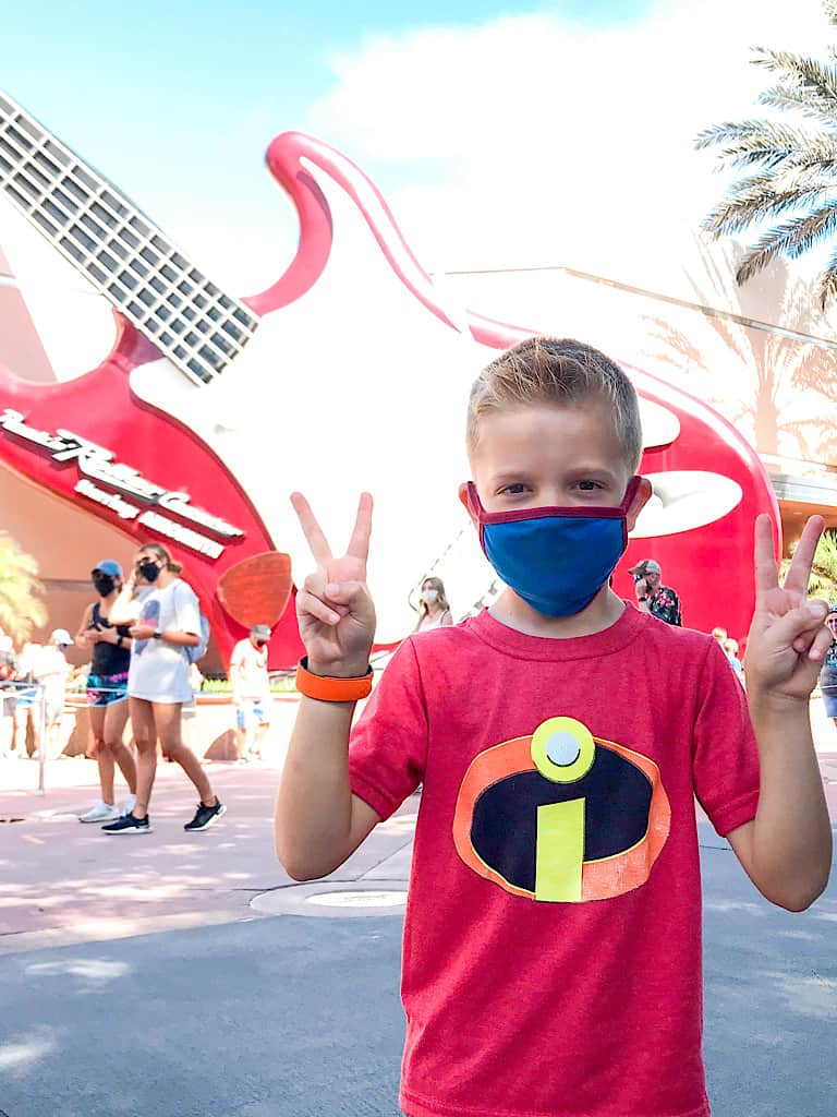 A boy holding up four fingers in front of Rock 'n Roller Coaster at Disney's Hollywood Studios at Disney World in Florida.