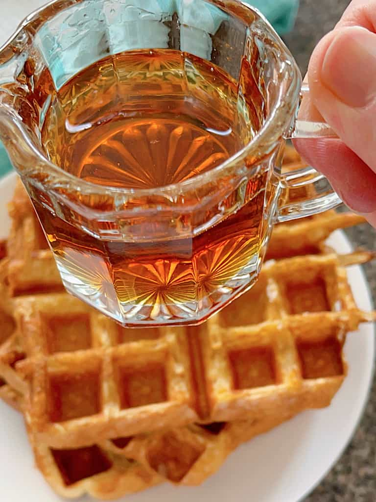 A cup of maple syrup over a stack of French Toast Waffles.