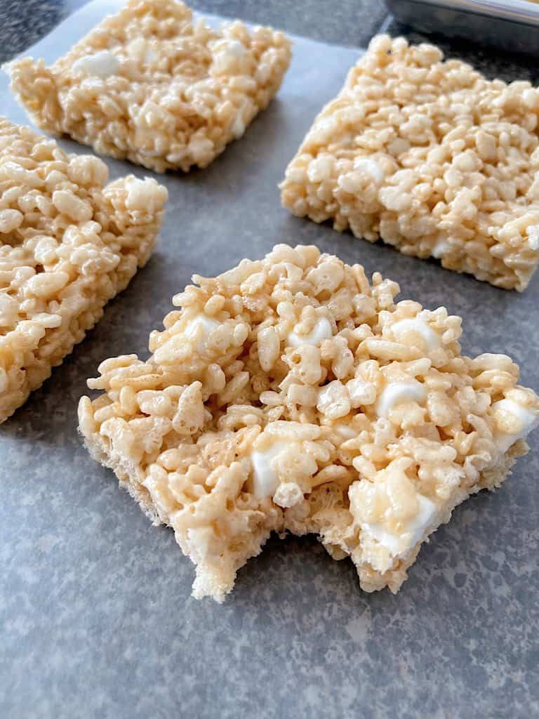 Four Rice Krispie Treats with one having a bite removed