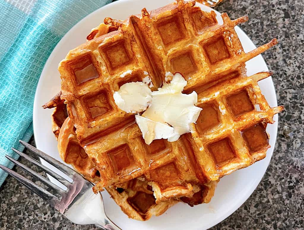 French Toast Waffles on a plate topped with butter next to a fork and a blue and white towel.