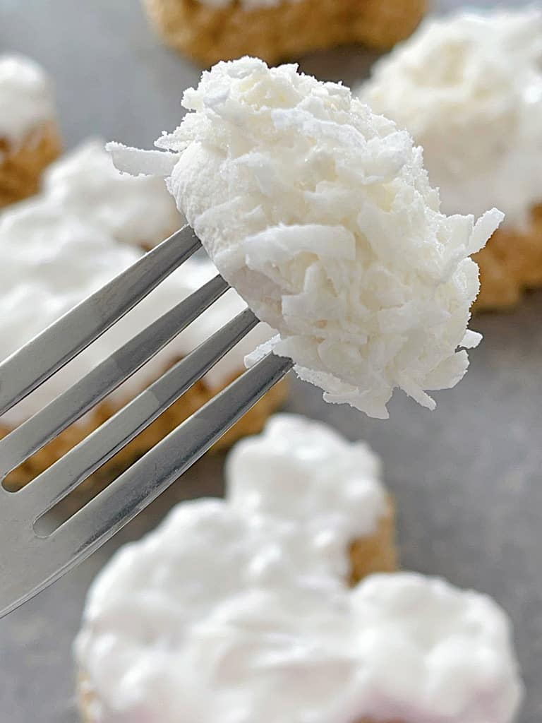 A fork holding a marshmallow covered in coconut flakes.
