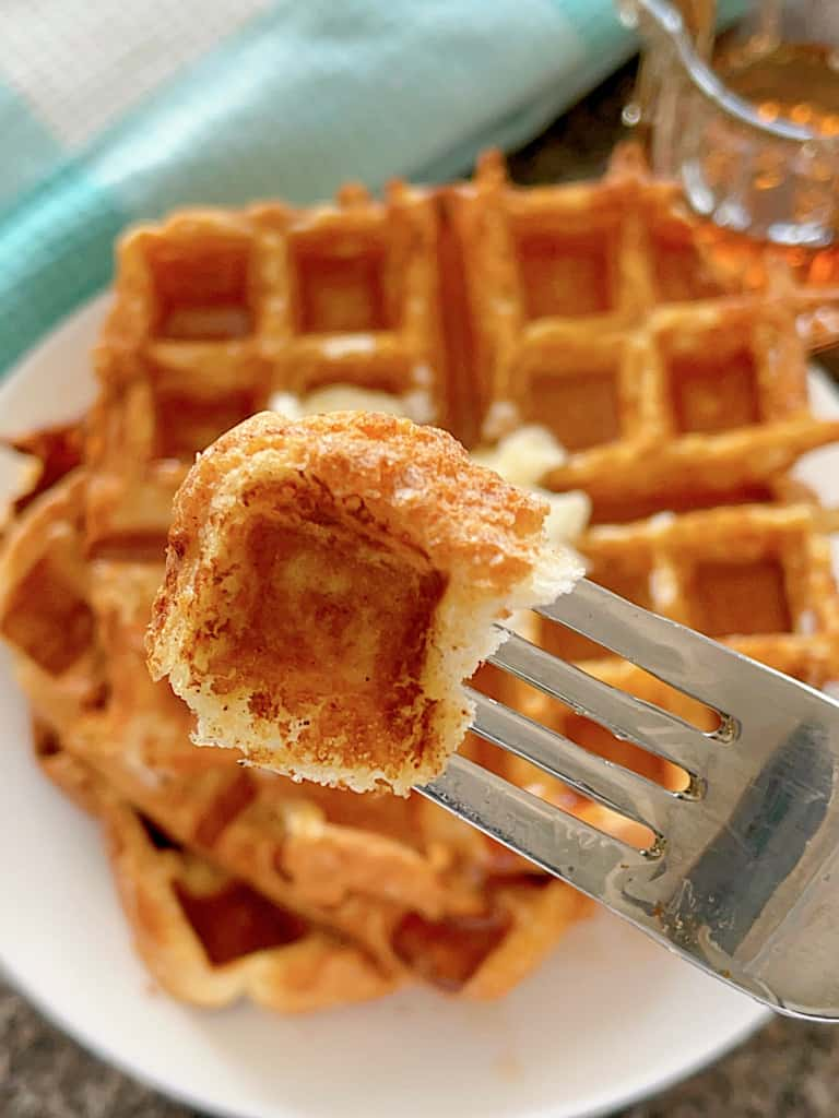 A fork holding a piece of French Toast Waffles.