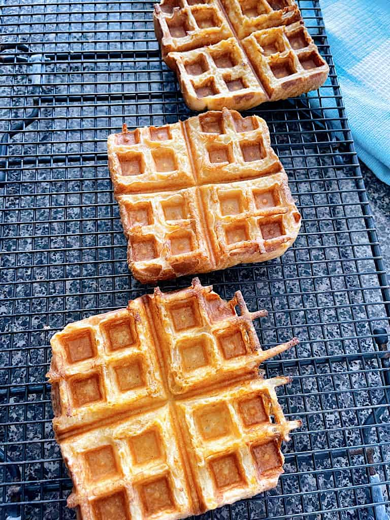 Three French Toast Waffles on a cooling rack.