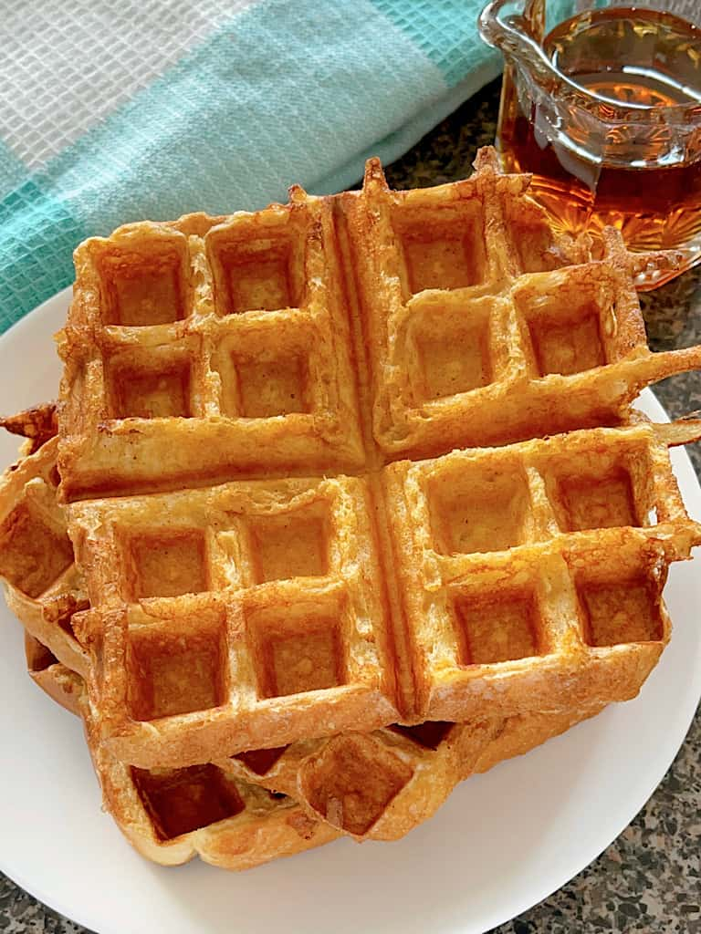 French Toast waffles stacked on a white plate.
