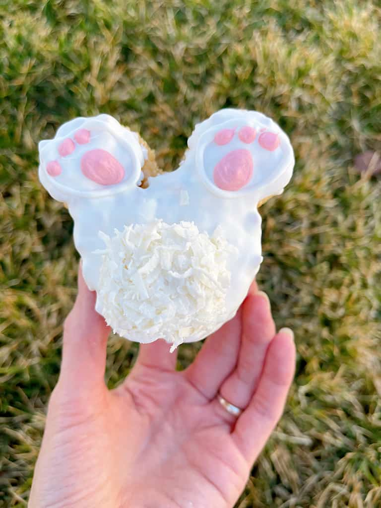 A hand holding a Mickey Mouse shaped Bunny Tail Rice Krispie Treat.
