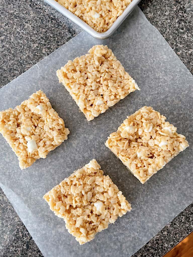 Four Rice Krispie Treat squares on a piece of parchment paper.