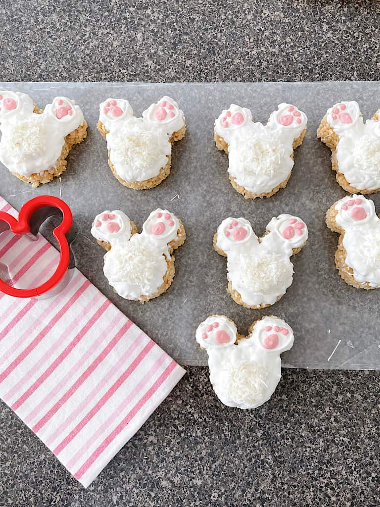 Eight Mickey Bunny Tail Rice Krispie Treats next to a pink and white towel and a Mickey Mouse cookie cutter.