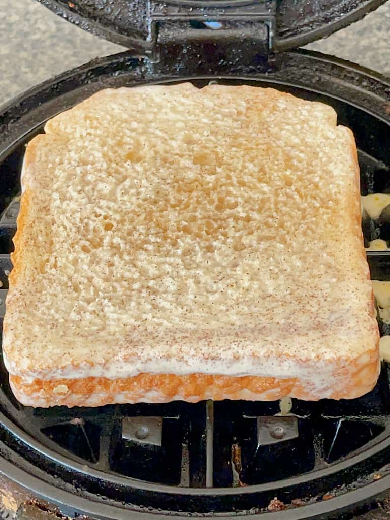 A slice of bread on a waffle iron.