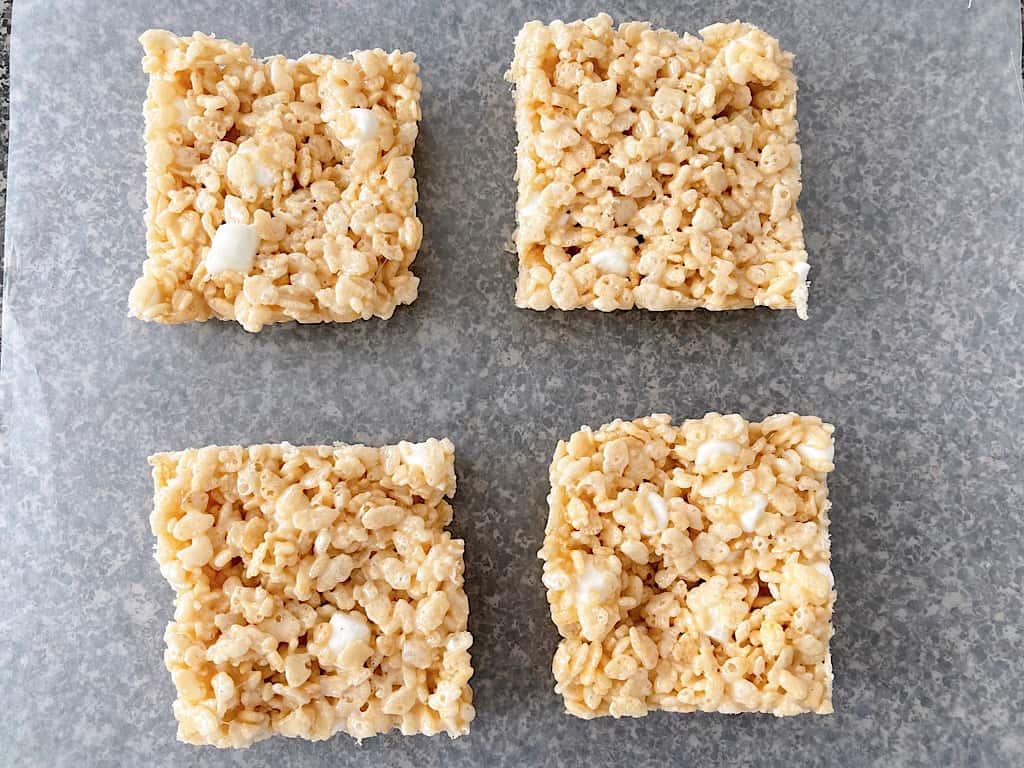 Four Rice Krispies Treats cut into squares on a piece of parchment paper.