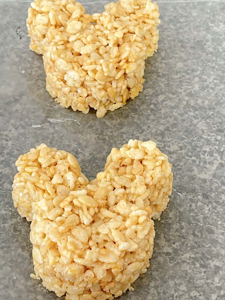 Two Mickey Mouse Rice Krispie Treats on wax paper.