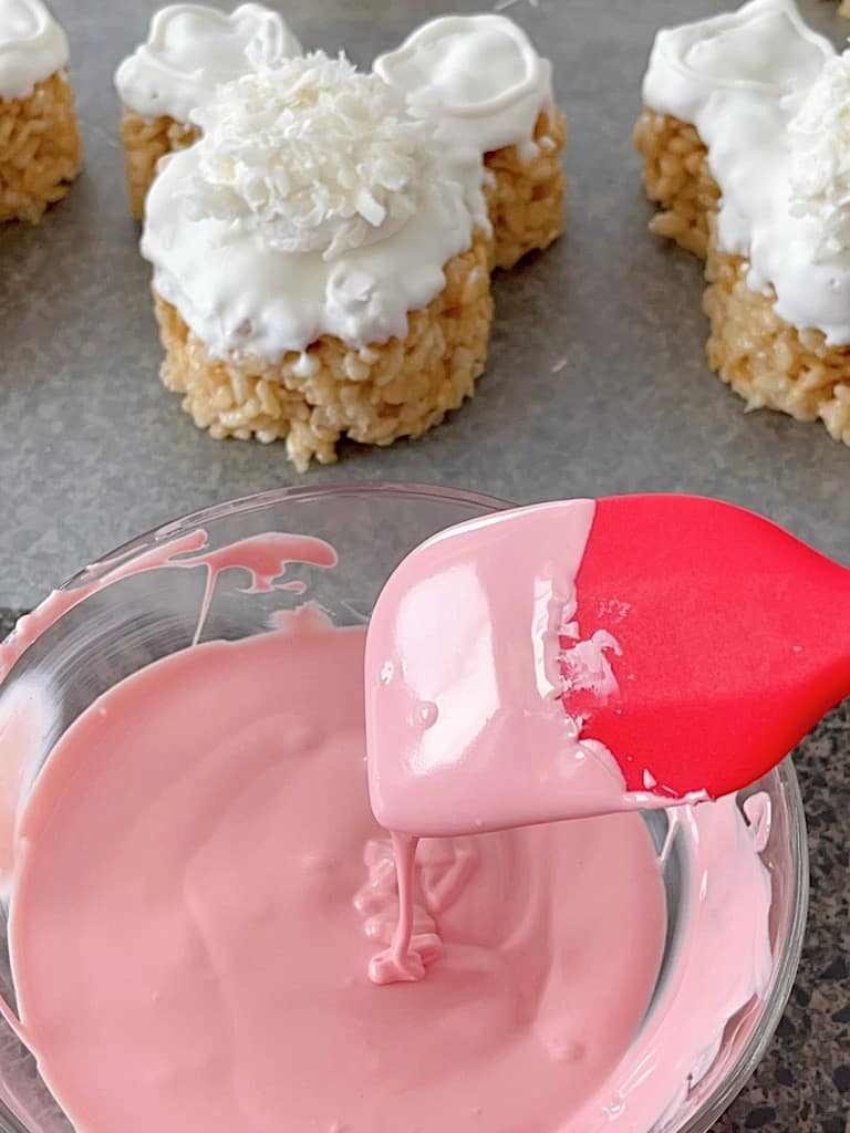 A spatula with a bowl of melted pink candy melts.