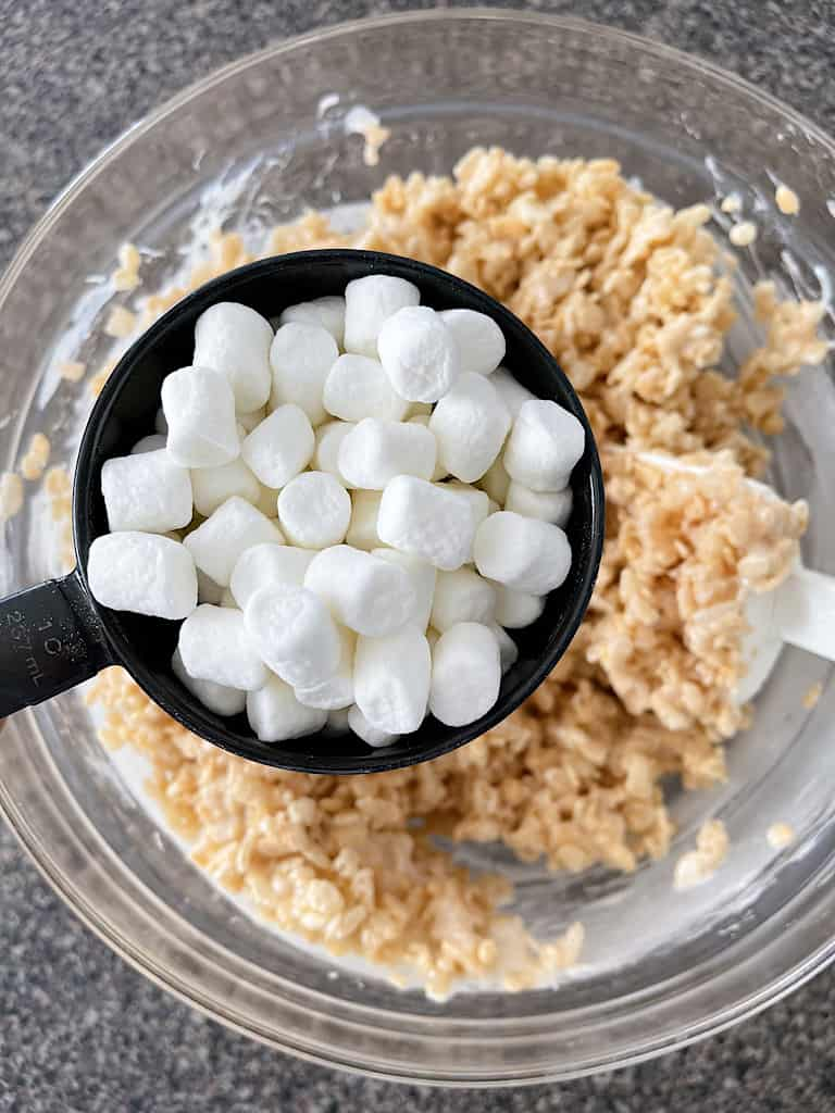 A measuring cup full of mini marshmallows over a bowl of Rice Krispie treats.
