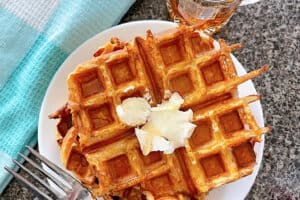 French Toast Waffles topped with butter on a white plate next to a blue and white towel and an empty syrup cup.
